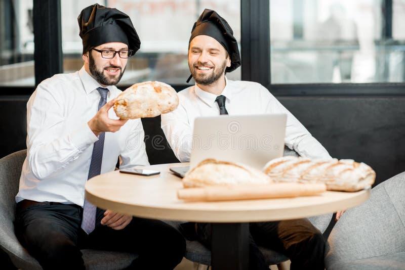 Bakkers die met brood in het bureau werken stock foto
