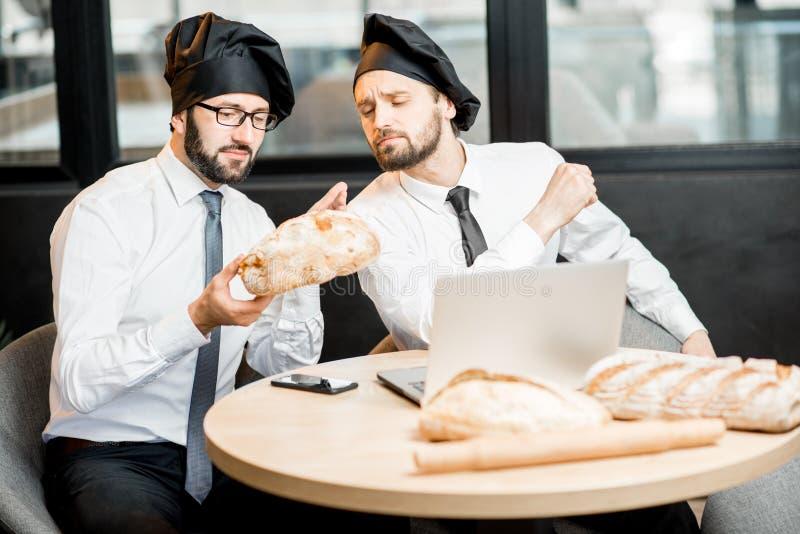 Bakkers die met brood in het bureau werken stock foto's