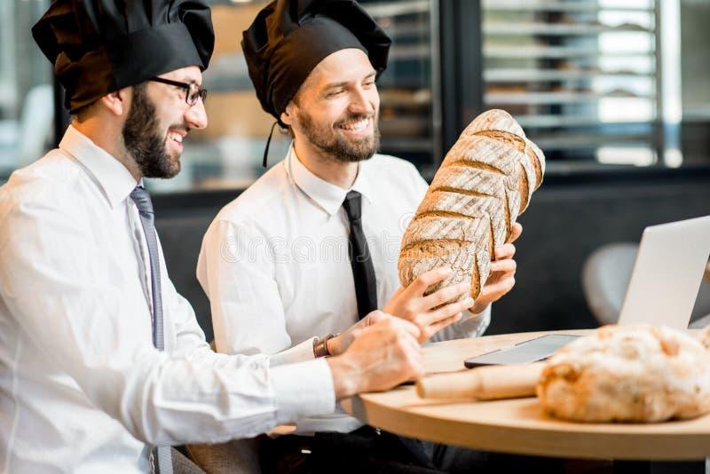 Bakkers die met brood in het bureau werken royalty-vrije stock fotografie