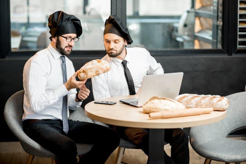 Bakkers die met brood in het bureau werken stock afbeelding