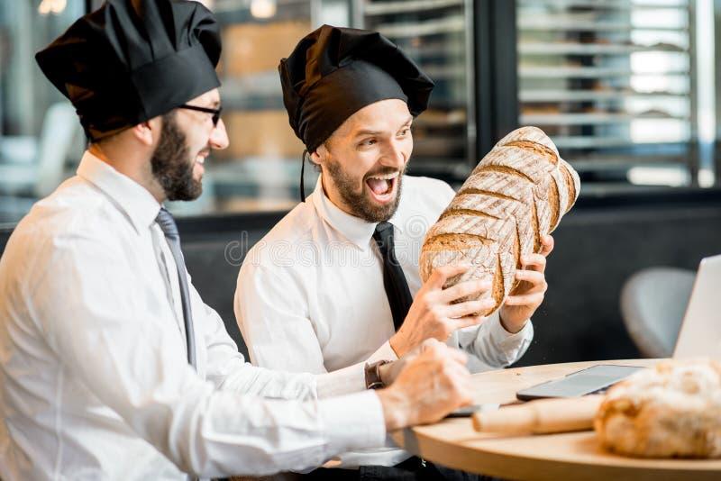 Bakkers die met brood in het bureau werken royalty-vrije stock afbeelding