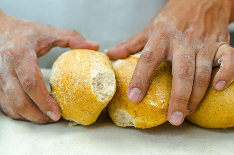 Bakkershanden die verse heerlijke broodjes van brood tegen elkaar stapelen stock foto