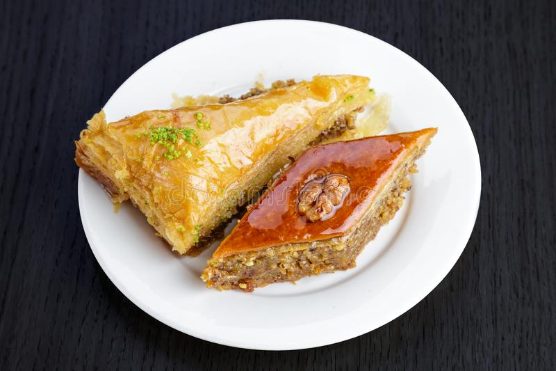 Baklava araba tradizionale del dessert con le noci ed il cardamomo, su una tavola di legno Baklava casalinga con i dadi ed il mie immagine stock
