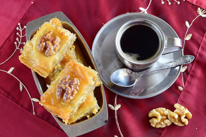 Baklava grego tradicional feito com massa do filo, xarope de açúcar e wallnuts em uma bandeja do metal com o copo de café do meta imagens de stock royalty free