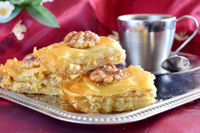 Baklava grego tradicional feito com massa do filo, xarope de açúcar e wallnuts em uma bandeja do metal com o copo de café do meta foto de stock