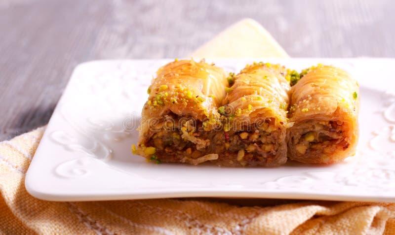Baklava mit Pistazien und Honig auf Platte lizenzfreie stockfotografie