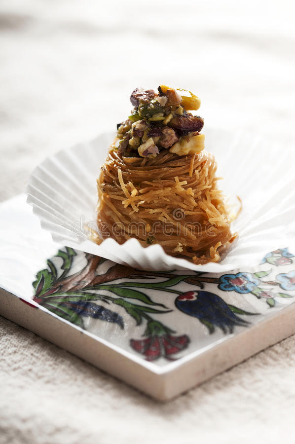 Baklava pieces with nut mix. On a oriental pattern stock photography