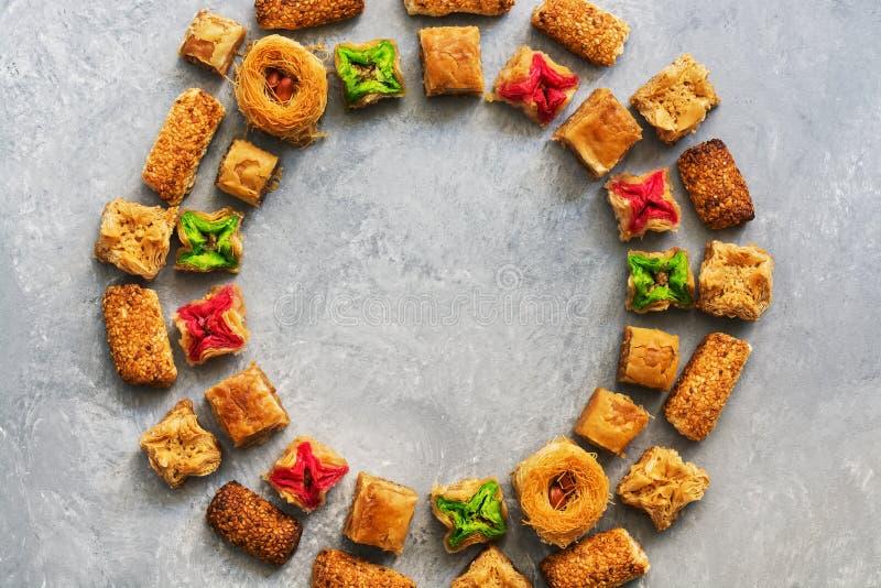 Baklava tradizionale del Medio-Oriente del dessert su un fondo grigio Struttura rotonda dei dolci arabi Vista da sopra fotografie stock libere da diritti