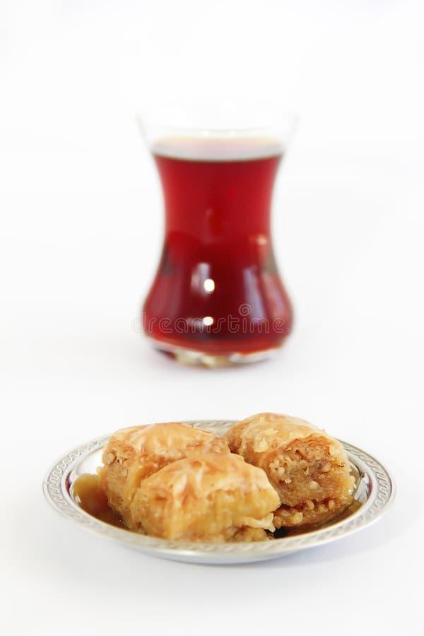 Baklava turca nazionale tradizionale di dolcezza sul piatto decorativo e su un vetro di tè immagini stock libere da diritti