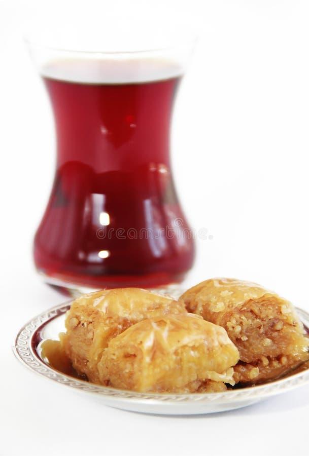 Baklava turca nazionale tradizionale di dolcezza sul piatto decorativo e su un vetro di tè immagini stock