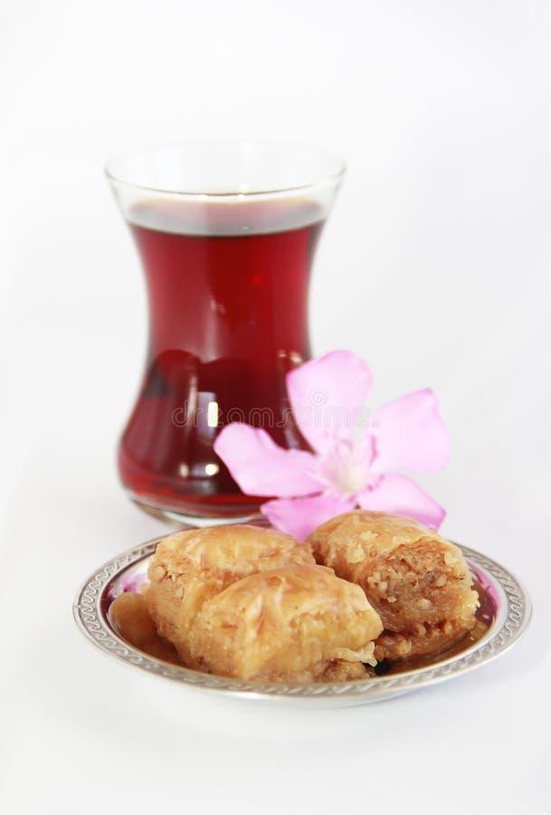 Baklava turca nazionale tradizionale di dolcezza sul piatto decorativo e su un vetro di tè fotografia stock libera da diritti