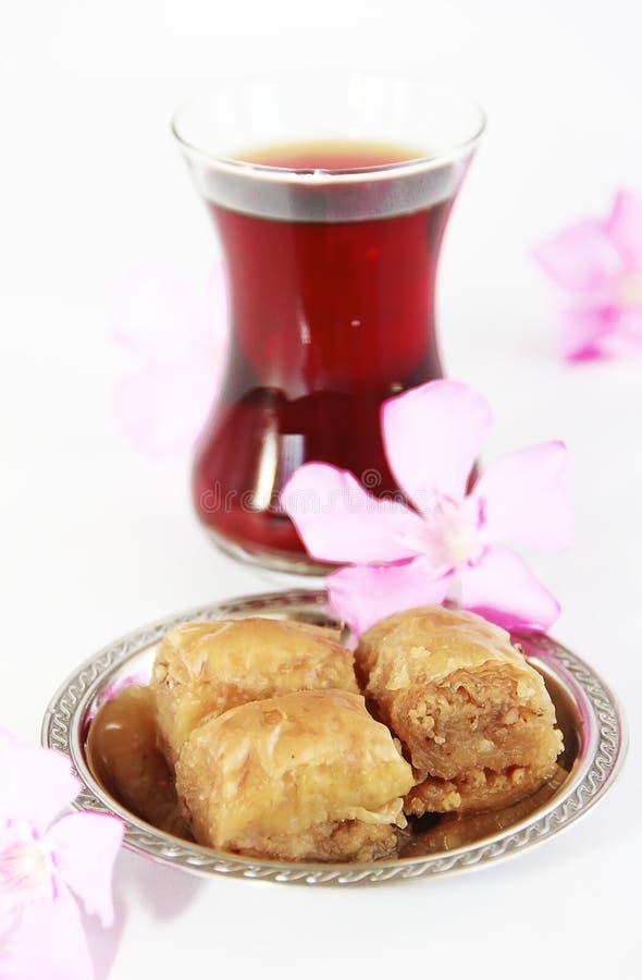 Baklava turca nazionale tradizionale di dolcezza sul piatto decorativo e su un vetro di tè fotografie stock