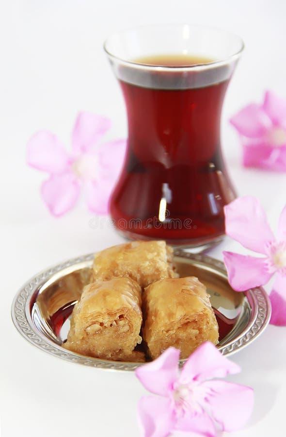 Baklava turca nazionale tradizionale di dolcezza sul piatto decorativo e su un vetro di tè immagine stock libera da diritti