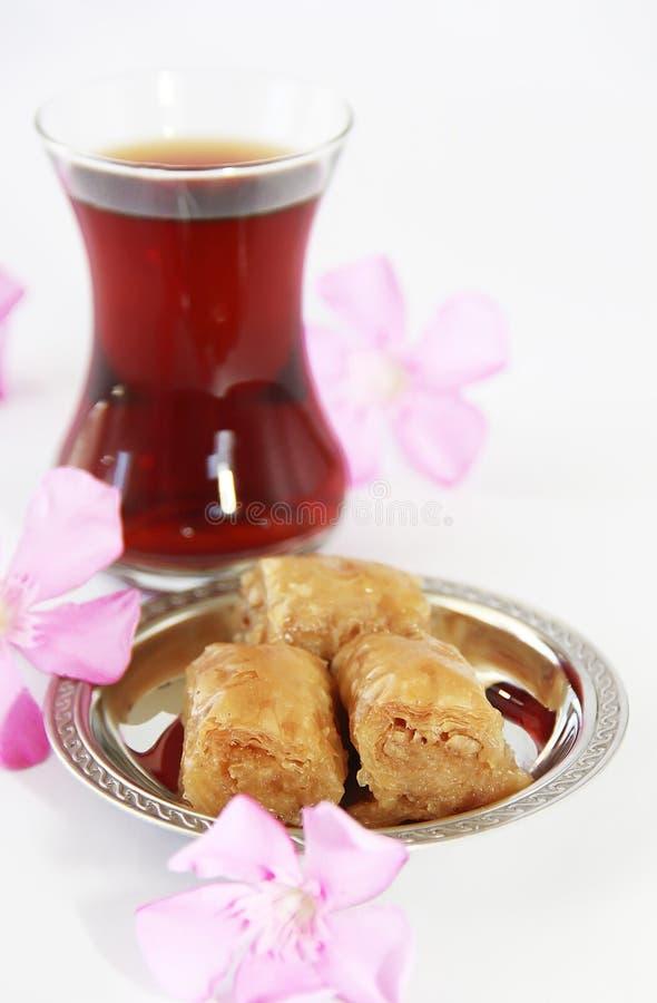 Baklava turca nazionale tradizionale di dolcezza sul piatto decorativo e su un vetro di tè immagine stock