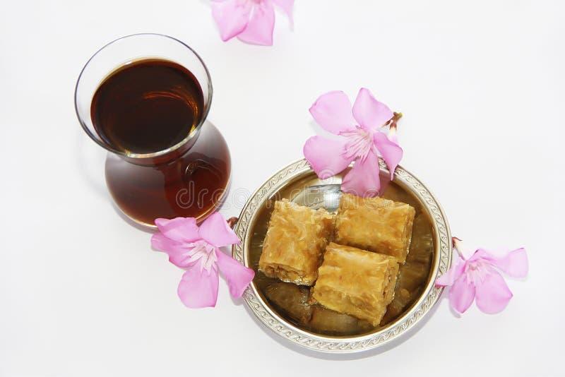 Baklava turca nazionale tradizionale di dolcezza sul piatto decorativo e su un vetro di tè fotografie stock libere da diritti