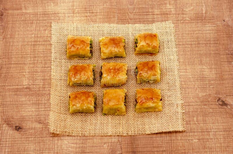 Baklava turco da sobremesa no teste padrão de madeira da placa foto de stock