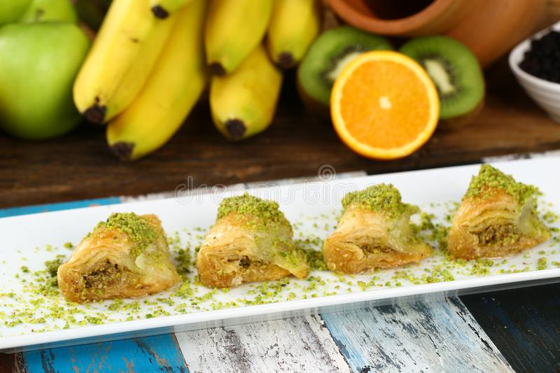 Baklava. Turkish baklava on the plate and fruits background royalty free stock images