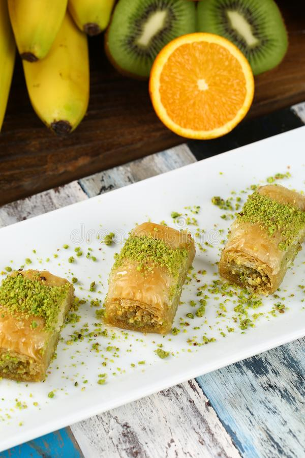 Baklava. Turkish baklava on the plate and fruits background stock photography