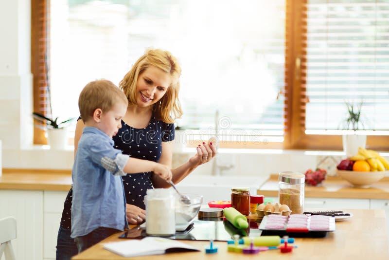 Bakning för härligt barn och moder royaltyfria bilder