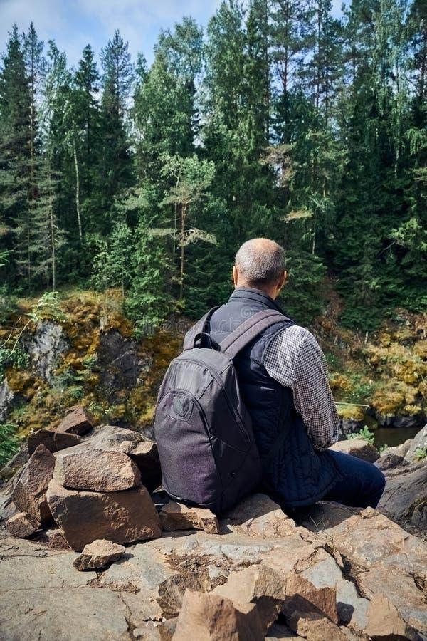 Bakom av den unga mannen beundrar den nordliga naturen Personen som sitter på bakgrund av, vaggar, stenar, bakre sikt royaltyfria foton