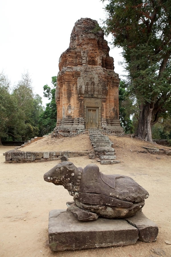 Bakong temple ruins. Nandi, the Shiva bull, and brick tower in the enclosure of the Bakong temple ruins, Angkor, Siem Reap, Cambodia. The temple is part of the stock photo