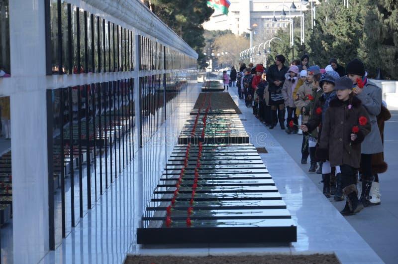BAKOU, AZERBAÏDJAN - 20 JANVIER 2011 fleurs étendues à l'égard par des personnes en deuil sur les tombes de marbre au monument du photographie stock