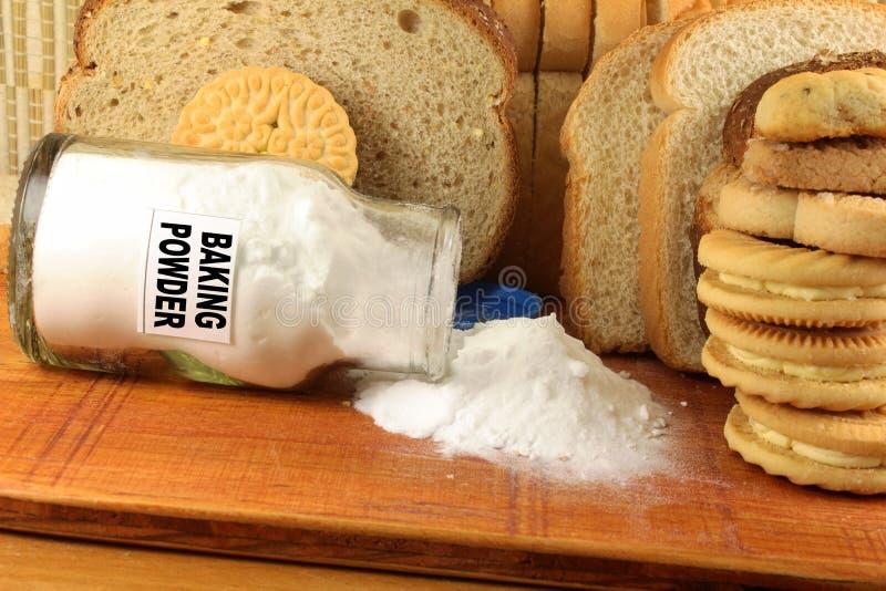 Bakpulver i en glass krus med kakan och bröd royaltyfri foto
