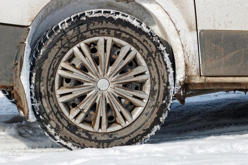 Bakre hjul av det smutsiga bilanseendet i snöcloseupen royaltyfria foton