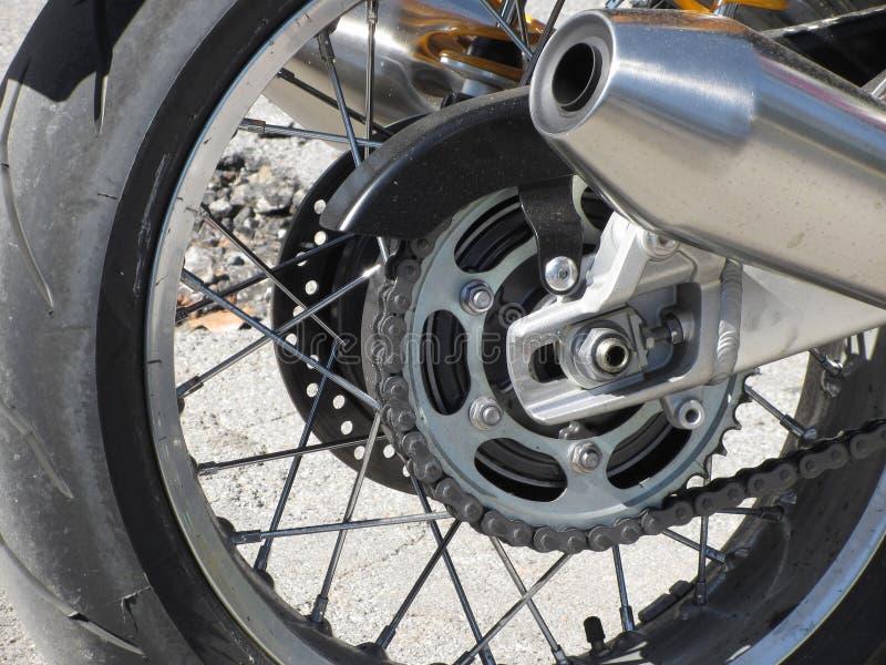 Bakre hjul och chromed avgasrörrör av en klassisk motorcykel Slapp fokus royaltyfria foton