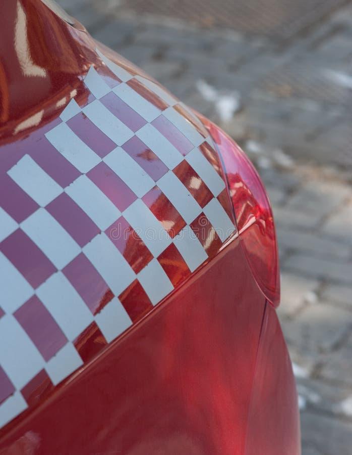 Bakre ljus av en röd sportbil med en rutig flaggagarnering arkivbilder