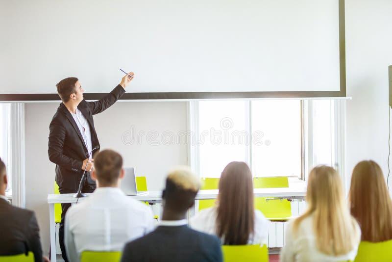 Bakre sikt av åhörare i mötet för konferenskorridor eller seminariumsom har högtalare på etappen, affären och utbildningen omkrin arkivfoton