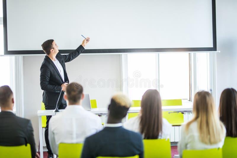 Bakre sikt av åhörare i mötet för konferenskorridor eller seminariumsom har högtalare på etappen, affären och utbildningen omkrin arkivbild