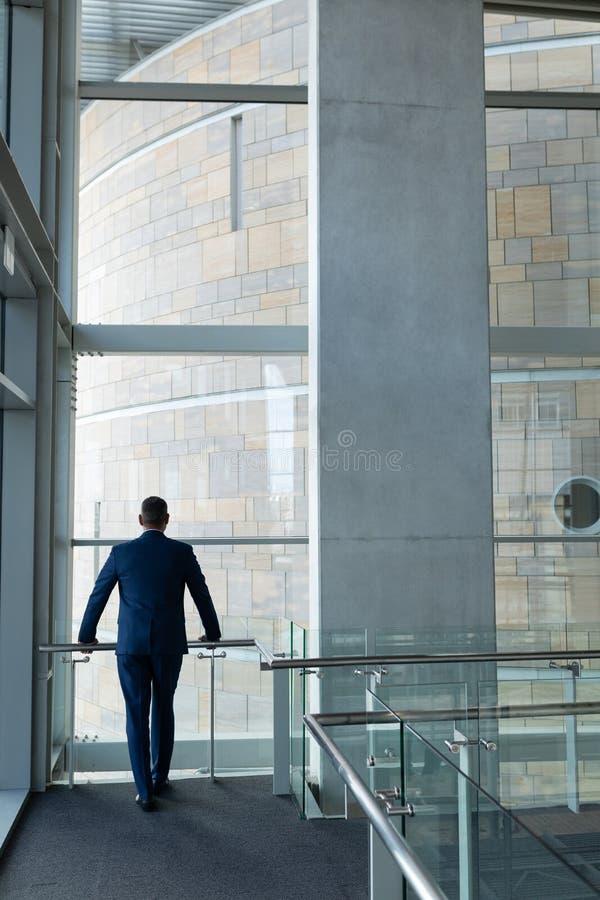 Bakre sikt av affärsmananseendet på det första golvet av kontoret och som lutar på räcket som ser thr royaltyfria bilder