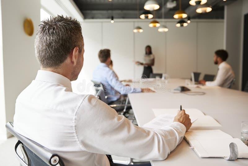 Bakre sikt av affärsmannen Listening To Presentation i modern styrelse royaltyfri foto