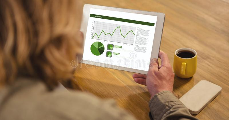Bakre sikt av affärsmannen som analyserar grafer på den digitala minnestavlan royaltyfria foton