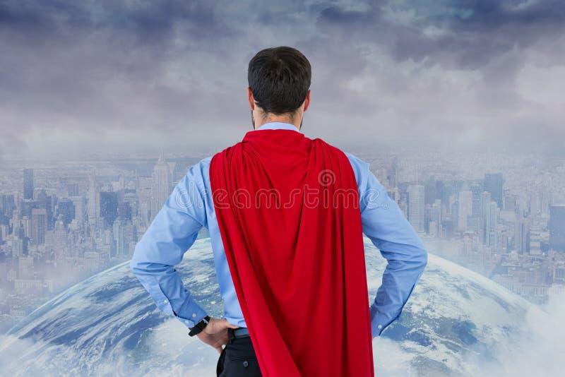 Bakre sikt av affärsmannen som bär udde för toppen hjälte, medan se staden och jordklotet stock illustrationer