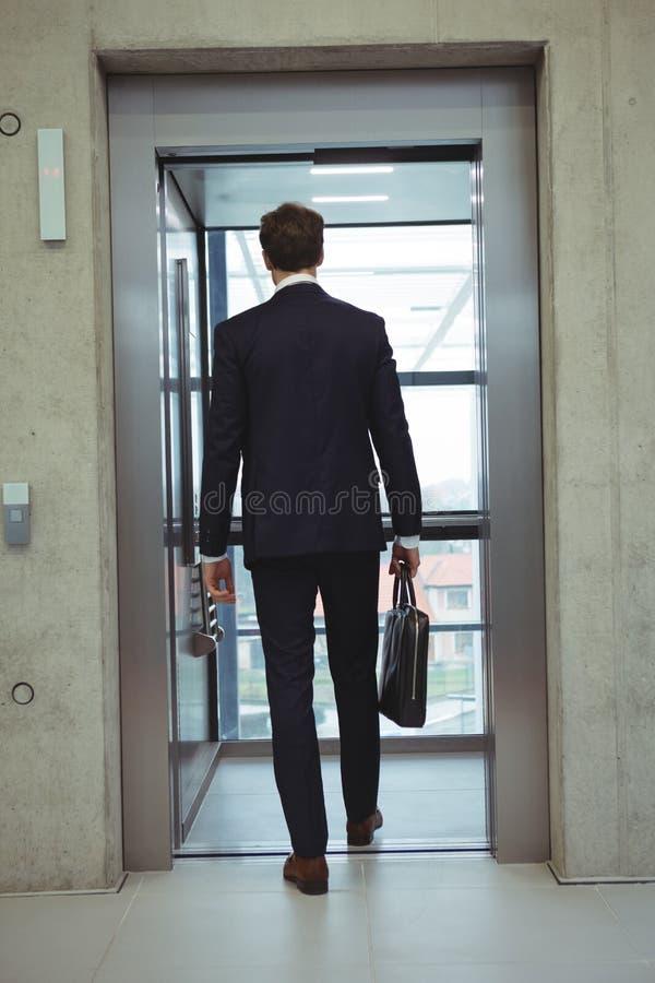 Bakre sikt av affärsmannen som går in i en hiss royaltyfri foto