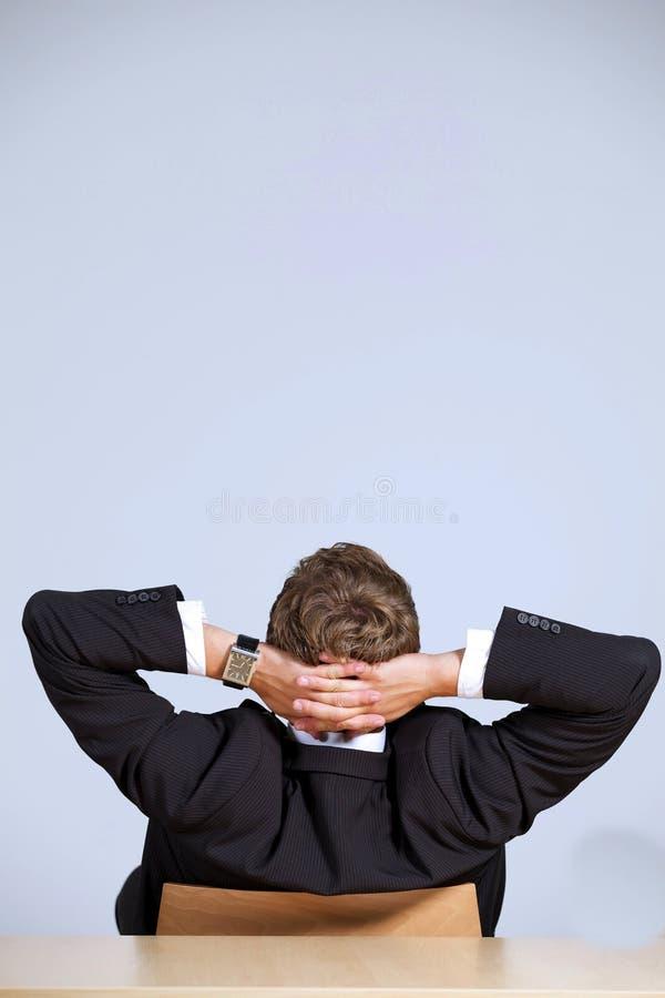 Bakre sikt av affärsmannen som i regeringsställning sitter med händer bak huvudet fotografering för bildbyråer
