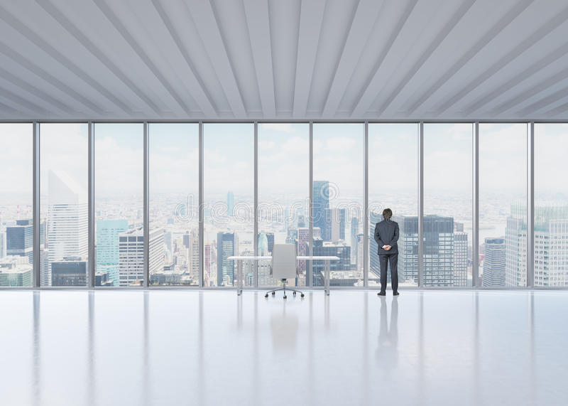 Bakre sikt av affärsmannen som ser ut fönstret i News York panorama- kontor royaltyfria bilder