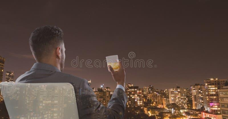 Bakre sikt av affärsmansammanträde på hållande exponeringsglas för stol av alkohol och att se staden royaltyfri fotografi