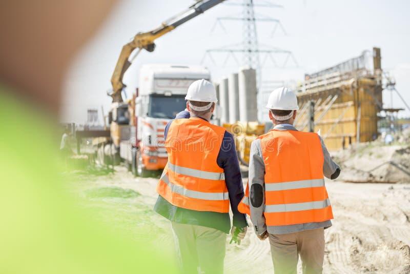 Bakre sikt av arbetsledare som går på konstruktionsplatsen royaltyfria foton