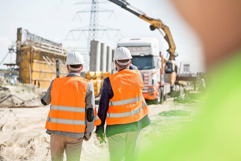 Bakre sikt av arbetsledare som går på konstruktionsplatsen royaltyfri fotografi