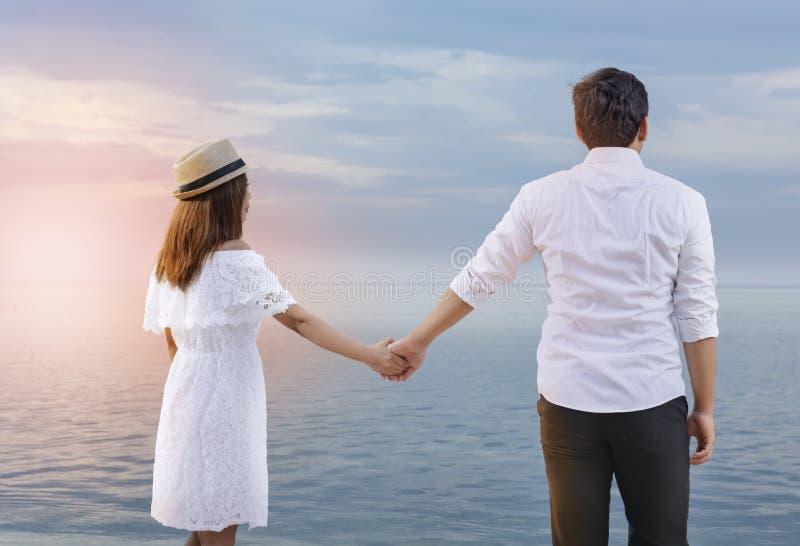 Bakre sikt av asiatiska romantiska par som tillsammans rymmer händer på stranden arkivbilder