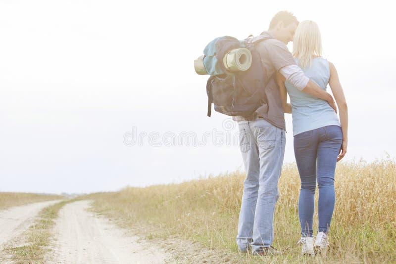 Bakre sikt av att älska fotvandra par som tillsammans står på fältet royaltyfri foto