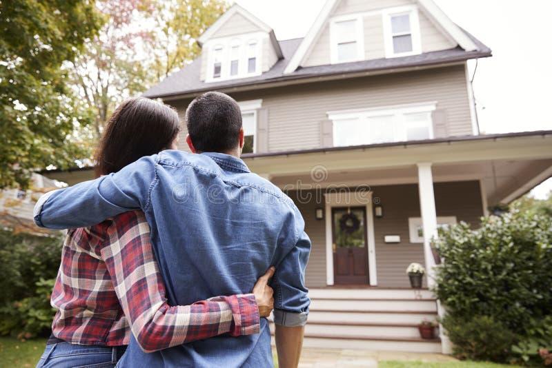 Bakre sikt av att älska par som ser huset arkivfoton