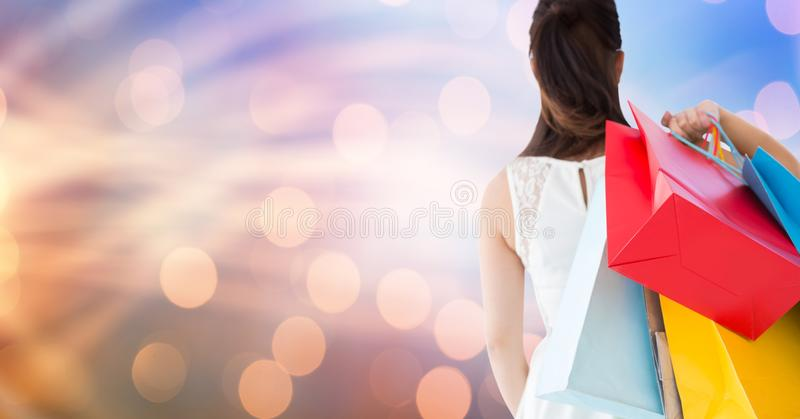 Bakre sikt av bärande shoppingpåsar för kvinnlig över bokeh arkivbilder