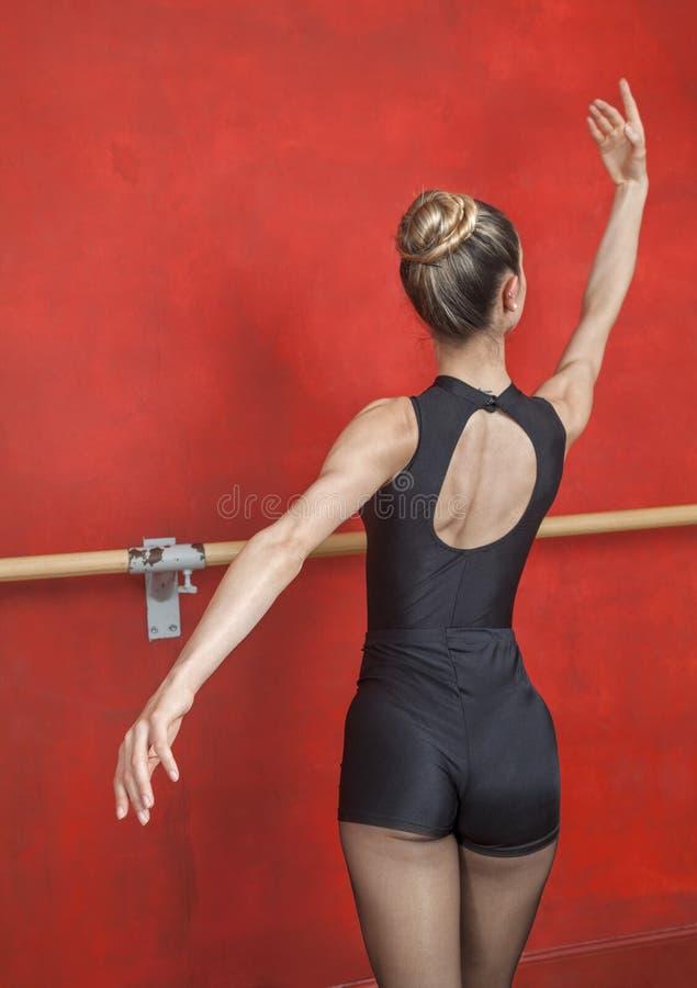 Bakre sikt av ballerina som öva mot den röda väggen arkivbild