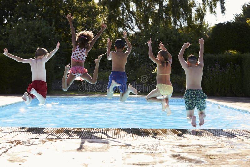 Bakre sikt av barn som hoppar in i utomhus- simbassäng royaltyfria bilder