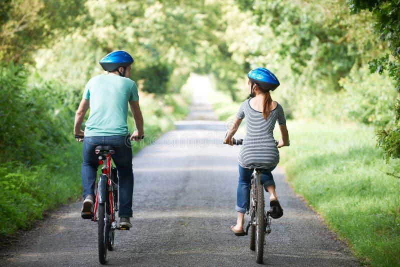 Bakre sikt av barnpar som cyklar på landsgränd royaltyfri foto