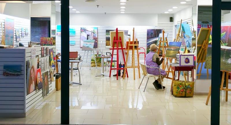 Bakre sikt av bilden för kvinnakonstnärmålning i studio arkivbild